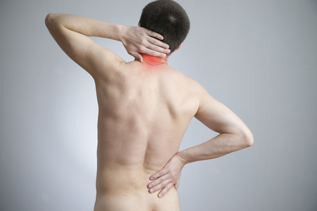 Pain in a body of the man on gray background. Red dot photo