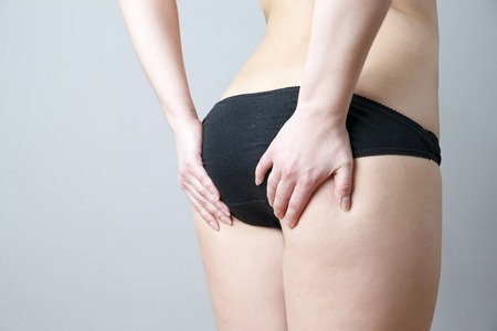 Buttocks massage against cellulite. Fatty female hips. Skin care, cellulite. Obesity photo