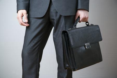 灰色の背景に手でブリーフケースを持ったビジネスマン 写真素材