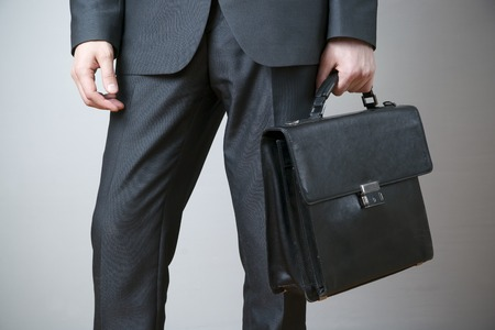 Businessman with briefcase in hand on gray background