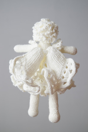 openwork: White knitted angel on a gray background. Toy from wool