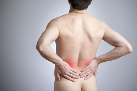 pyelonephritis: Pain in a back of the man on gray . Red dot