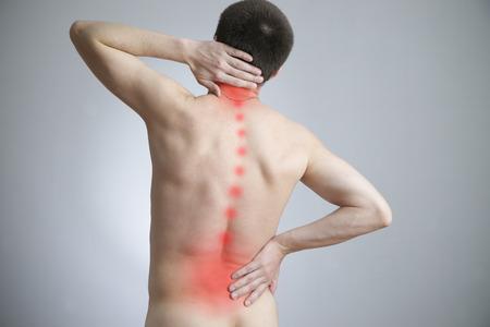 Schmerzen in einem Körper des Mannes auf grau. Red dot