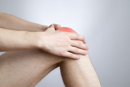 Knee pain in men on gray  photo