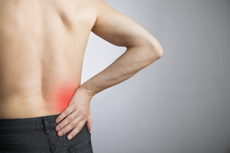 Pain in the lower back in men on gray  Stock Photo