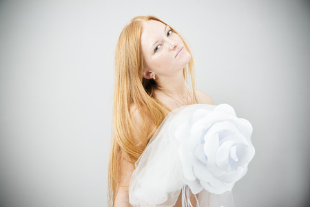 Portrait of red-haired woman with paper flower on a gray background photo