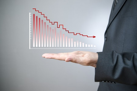 decrease: Business concept. Businessman presenting a sustainable decrease development on a bar chart on gray .