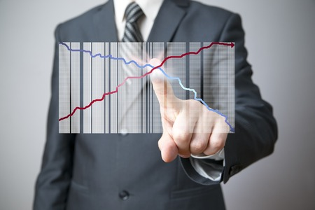 Business concept. Businessman presenting a successful sustainable development on a bar chart on gray background. photo
