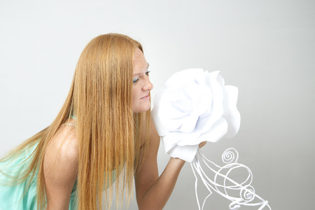 Portrait of red-haired woman with paper flower on a gray  photo