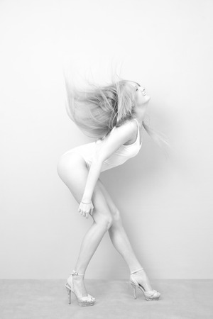 Portrait of a woman in bodysuit on a gray  photo