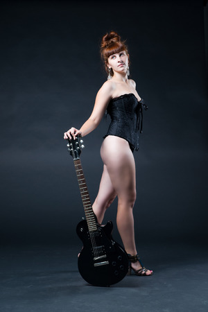 no heels: Young woman with an electric guitar in the studio Stock Photo