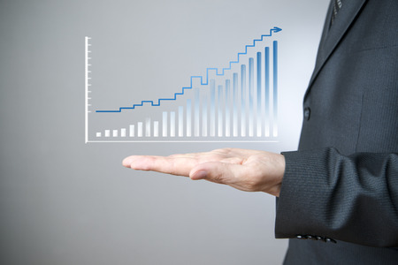 Business concept. Businessman presenting a successful sustainable development on a bar chart on gray .