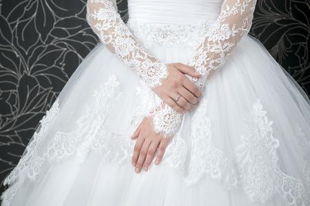 긴 소매 흰색 웨딩 드레스를 레이스. 여성의 손.