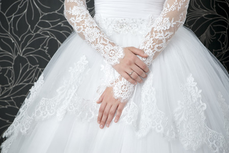 Lace white wedding dress with long sleeves. Women's hands.