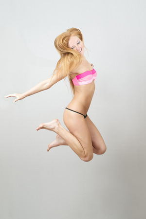 Happy beautiful woman jumping in swimsuit. Portrait of a young girl on a gray background. photo