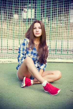 Beautiful young woman on the football field  Girl sitting on the green grass on the playground photo