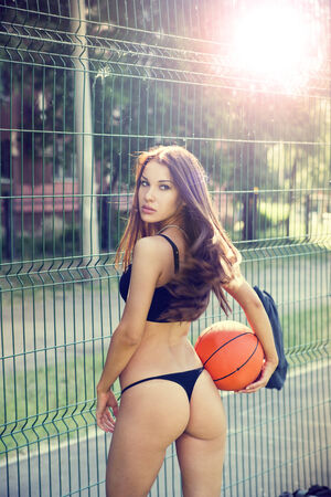 Beautiful young woman with fluttering hair playing basketball outdoors   The girl on the sports ground photo