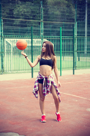 Beautiful young woman playing basketball outdoors   The girl on the sports ground photo