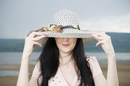 Portrait of a beautiful young woman in hat on the beach in summer photo