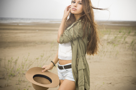 Young beautiful woman on a sandy beach on a cloudy day. photo