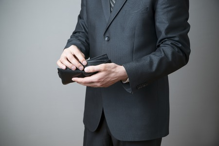Businessman with empty purse in hands on a gray background photo