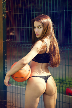 Beautiful young woman with fluttering hair playing basketball outdoors.  The girl on the sports ground