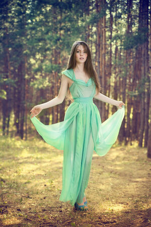 Portrait of a beautiful young woman in summer. Happy girl in a turquoise dress in a pine forest. photo