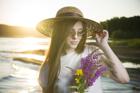 Portrait of a beautiful woman in a hat on a background of a sunset. Girl with a bouquet of flowers photo