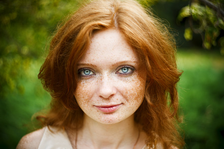 Portrait of redhead girl with blue eyes on nature. Face of young woman with freckles closeup photo