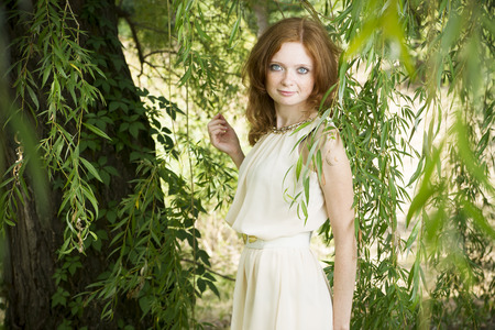 osier: Portrait of redhead girl with blue eyes on nature. Young woman in a dress on a background of osier. Stock Photo