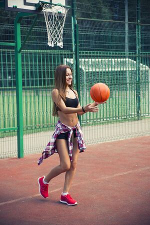 Beautiful young woman playing basketball outdoors.  The girl on the sports ground photo