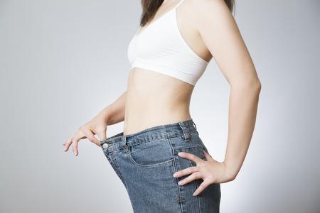 減量の概念。美しい女性スレンダーボディ。ジーンズ大きいサイズで若い女性。