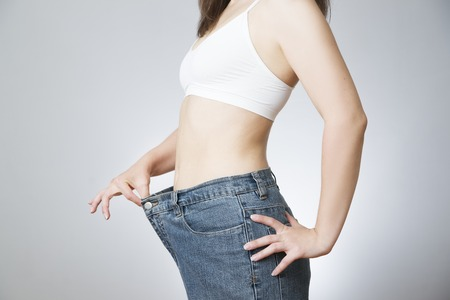 The concept of weight loss. Beautiful slender female body. Young woman in jeans large size. Foto de archivo