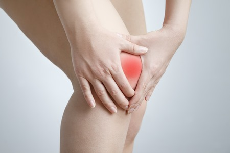 Knee pain of the woman on gray background.  Red dot. Stock Photo