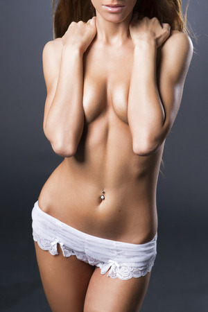 naked belly: Sexy body on a gray background. Naked beautiful young woman.