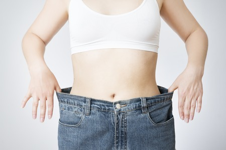 The concept of weight loss. Beautiful slender female body. Young woman in jeans large size. Banque d'images