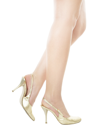 Slender legs gold shoes isolated on white background photo