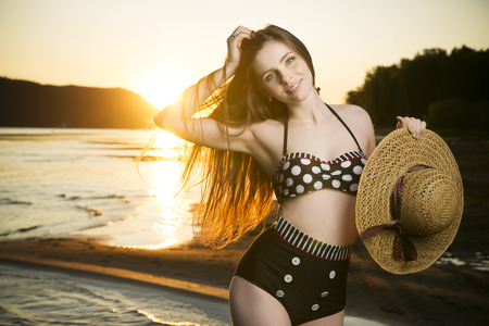 Beautiful woman in bikini on sunset background. Slim girl posing in a swimsuit Фото со стока - 31985076