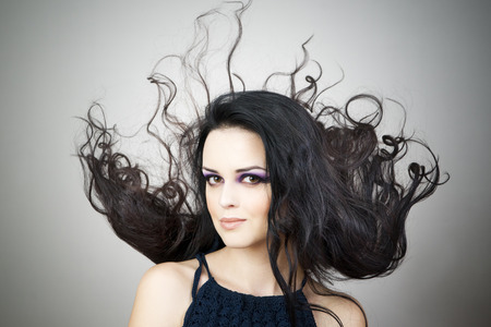Portrait of a beautiful young woman on a gray background. Professional make-up and hairstyle. photo