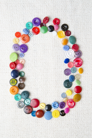 Letter O of the alphabet of buttons of various shapes and colors. Bright background for needlework. photo