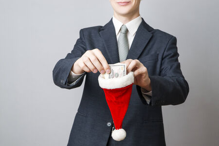 Businessman putting money in a Santa hat on gray background photo