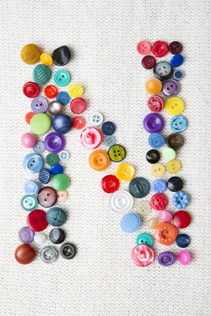Letter N of the alphabet of buttons of various shapes and colors. Bright background for needlework.