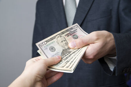 Money in the hands of the people. Convert dollars on gray background Stock Photo