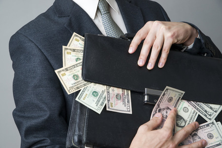 Businessman with a briefcase full of money in the hands of on gray background photo