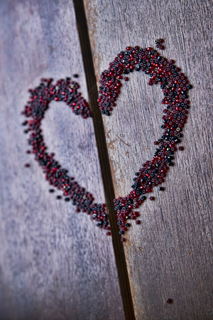 orifice: Background for Valentines day. Heart shape in a  heap of beads. Wooden pattern. Retro style. Stock Photo