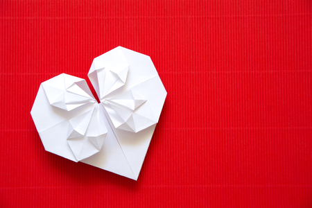 Heart made ​​of paper origami on red cardboard. Background   for Valentines day. photo