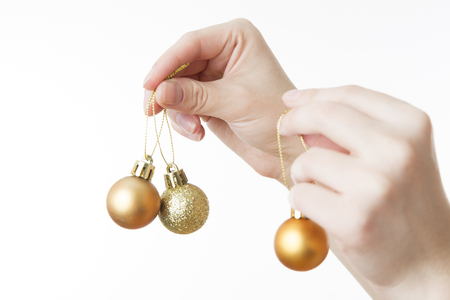 Christmas balls in female hands on a white background. New year. photo