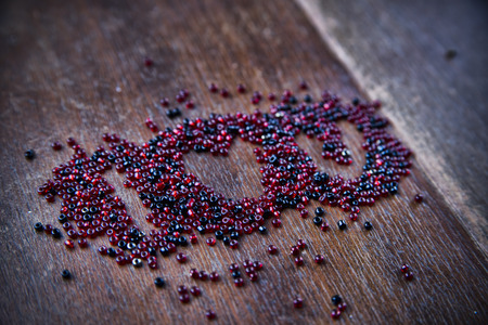 Background for Valentines day. Heart shape in a  heap of beads.  I love you. Wooden pattern. Retro style. Stock Photo