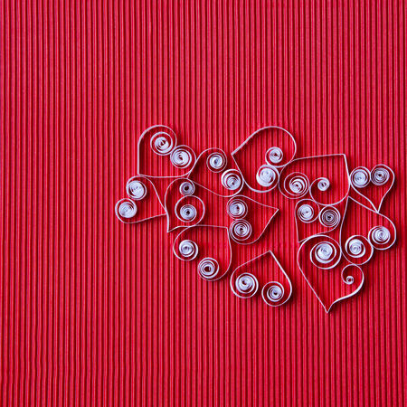 quilling: Quilling paper on red cardboard. Background with hearts for Valentines day.