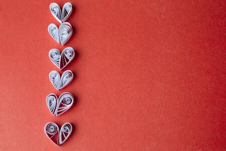 Quilling paper on red cardboard. Background with hearts for Valentines day. photo